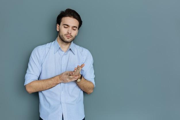 Concentré sur les pensées. joli jeune homme agréable debout sur fond gris et toucher sa main tout en étant attentionné