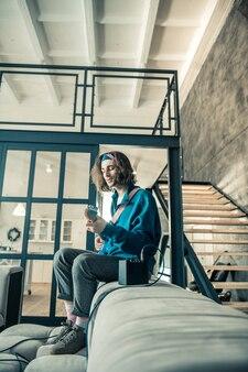 Concentré sur la performance. artiste talentueux aux cheveux longs expérimentant avec des sons et des styles tout en étant assis tout seul sur le canapé