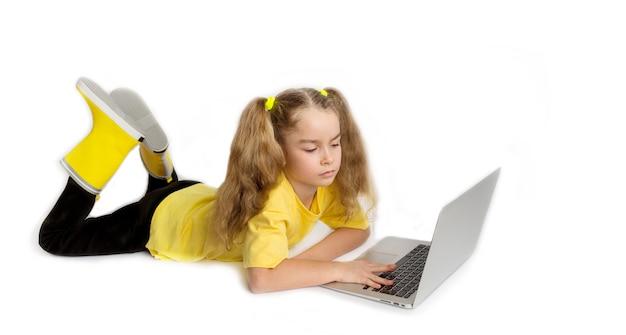 Concentré de petite fille européenne mignonne portant un t-shirt jaune allongé devant l'ordinateur, vérifiant les tâches dans la salle de classe en ligne, concept d'apprentissage à distance e-learning.