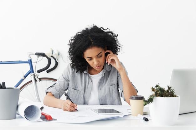 Concentré sérieux jeune femme architecte afro-américaine faisant des dessins