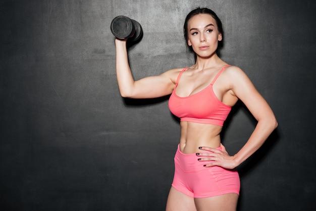 Concentré de sport jeune femme tenant des haltères.