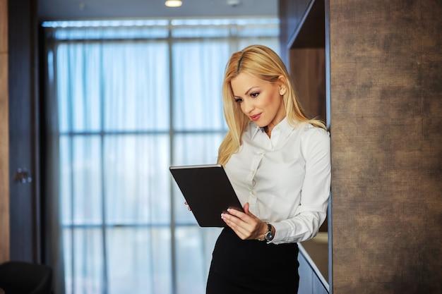 Concentré sur le travail. une belle jeune femme d'affaires formellement et joliment habillée utilise une tablette numérique tout en se tenant sur un intérieur moderne. des mains féminines tiennent une tablette, j'adore mon travail
