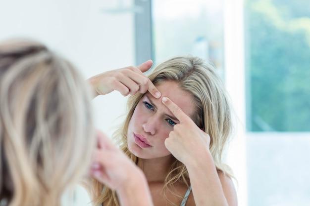 Concentrée belle jeune femme se regardant dans le miroir de la salle de bain à la maison