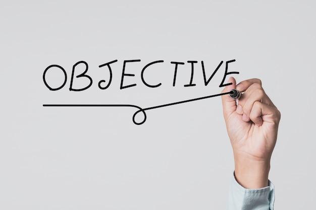 Concentrez la cible des objectifs de configuration et le but commercial. main qui écrit un libellé objectif à bord.