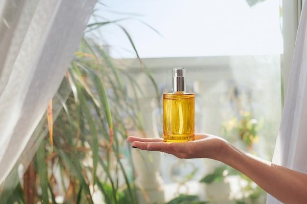 Concentrez-vous sur la bouteille de parfum sur la main de la femme.