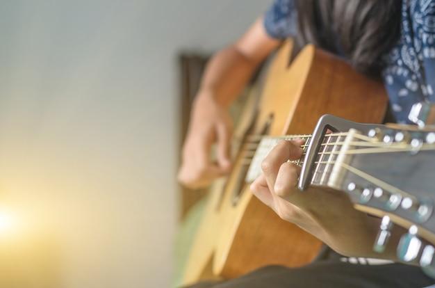 Concentrez-vous sur le doigt d'une fille jouant de la guitare acoustique à l'intérieur avec la lumière du soleil