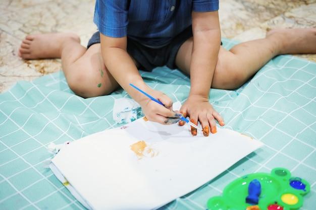 Concentrez-vous sur leurs mains sur du papier. les enfants utilisent des pinceaux pour dessiner leurs mains sur du papier afin de développer leur imagination et d'améliorer leurs compétences cognitives.