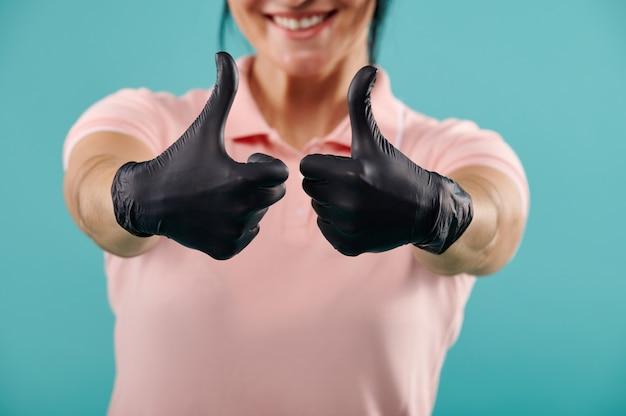Concentrez-vous sur les mains dans des gants en latex noirs montrant les pouces vers le haut. isolé sur fond bleu