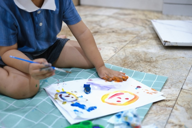 Concentrez-vous sur les mains sur papier, l'apprentissage de la petite enfance en utilisant des peintures et des pinceaux pour développer l'imagination et améliorer les compétences au tableau.