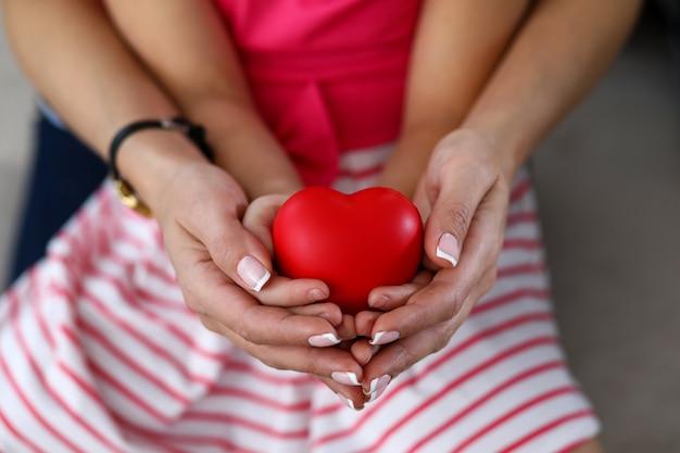 Concentrez-vous sur les tendres mains féminines tenant les paumes de bébé et le coeur rouge jouet. mère appréciant passer du temps heureux avec petite fille. concept de famille et de maternité