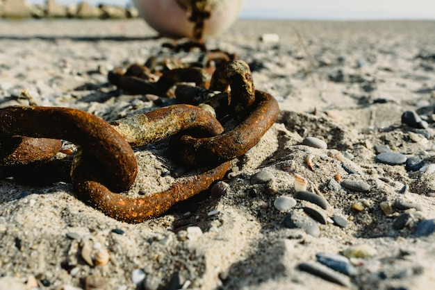 Concept d'abandon, vieilles chaînes rouillées et cassées jetées dans le sable d'une plage sale.