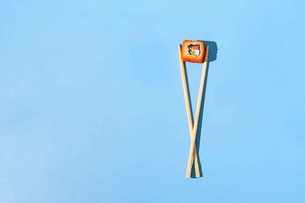 Un concept abstrait des baguettes en bois asiatique avec un rouleau de nourriture nationale sur la surface de couleur