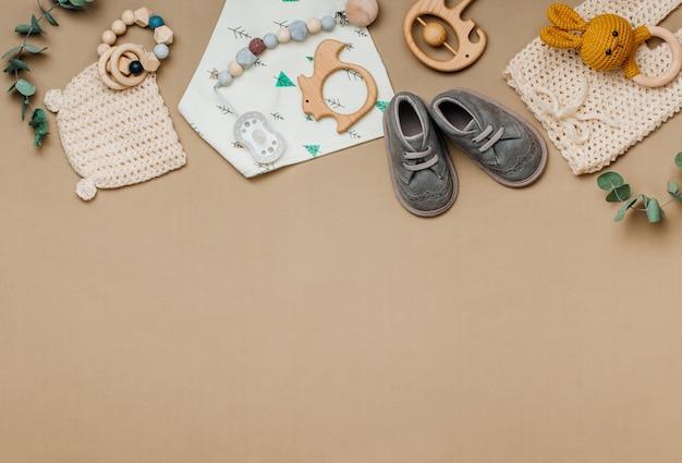 Concept d'accessoires en matériau naturel pour bébé. jouets en bois, vêtements et chaussures sur fond beige avec un espace vide pour le texte. vue de dessus, pose à plat.