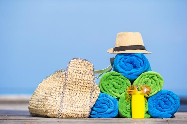Concept d'accessoires de vacances d'été et de plage - gros plan de serviettes colorées, chapeau, sac et protection solaire