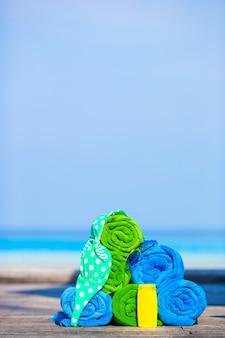 Concept d'accessoires de vacances d'été et de plage - gros plan de serviettes colorées, de lunettes de natation et de crème solaire