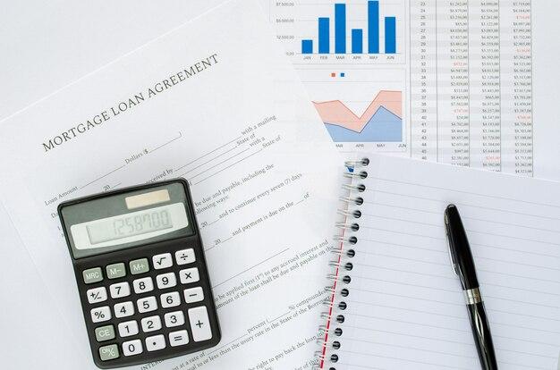 Concept d'accord de prêt hypothécaire avec calculatrice, bloc-notes, stylo et documents financiers. vue de dessus.