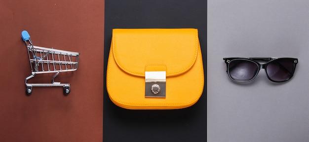 Concept accro du shopping minimaliste. sac en cuir jaune, mini lunettes de soleil trolley sur table en papier. accessoires de mode pour femmes. vue de dessus