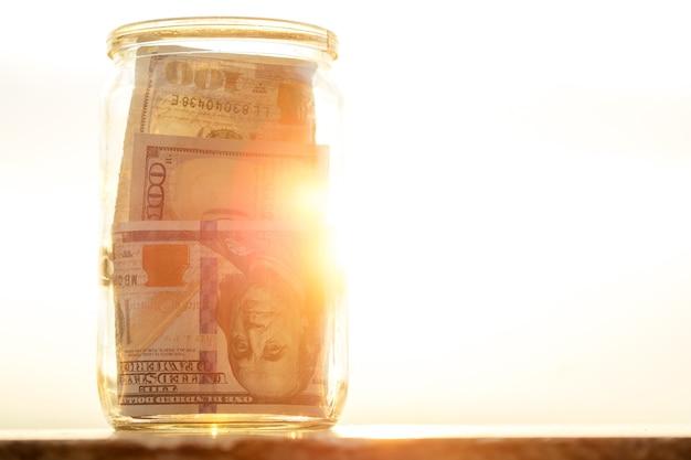 Concept d'accumuler de l'argent dans un bocal en verre au soleil avec l'aide du soleil