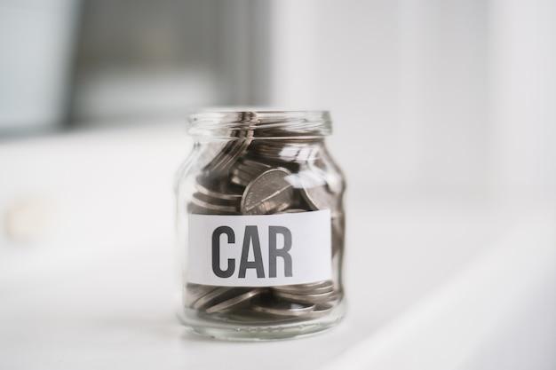 Le concept d'accumuler de l'argent pour une voiture - un bocal en verre avec des pièces.