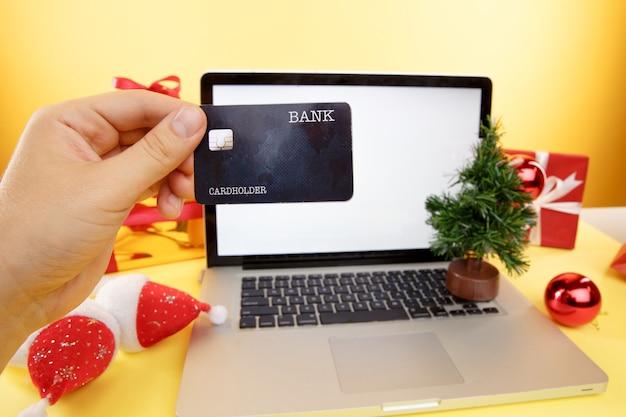 Concept d'achat en ligne. carte de crédit et ordinateur portable avec des cadeaux de noël et des boîtes.