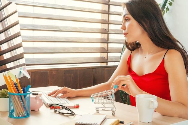 Concept d'achat en ligne avec une femme assise à la table d'accueil avec un écran d'ordinateur