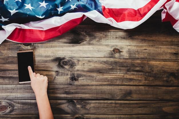 Concept d'achat en ligne - image d'une main indiquant un smartphone ou un téléphone portable sur un fond en bois avec un drapeau américain.
