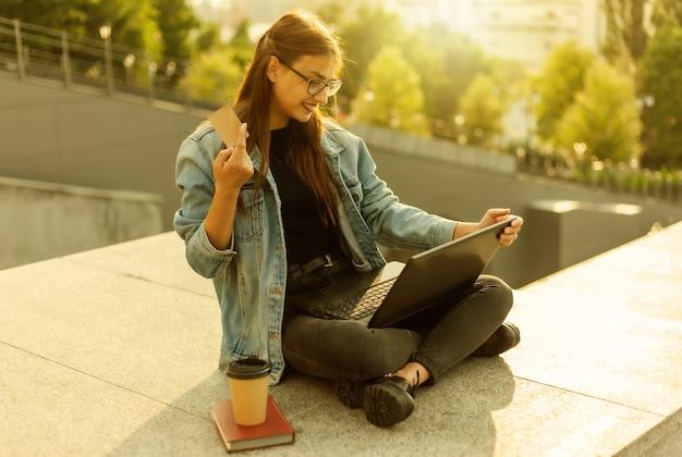 Concept d'achat en ligne. jeune femme moderne dans une veste en jean et des lunettes tient une carte de crédit à la main et un paiement en ligne avec un ordinateur portable à l'extérieur de la ville