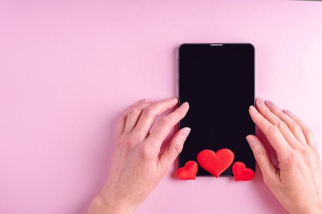 Concept d'achat en ligne. mains féminines sur un écran de tablette vierge noir avec forme de coeur rouge