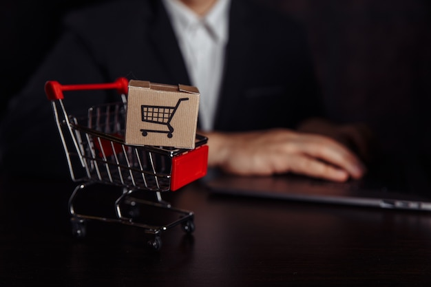 Concept d'achat en ligne. ordinateur portable avec chariot mini-marché et deux boîtes en papier