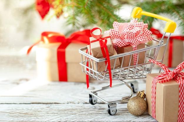 Concept d'achat en ligne - panier d'achat complet et coffrets cadeaux. chariot plein de différentes boîtes-cadeaux de noël avec ruban rouge sur fond de bois blanc.