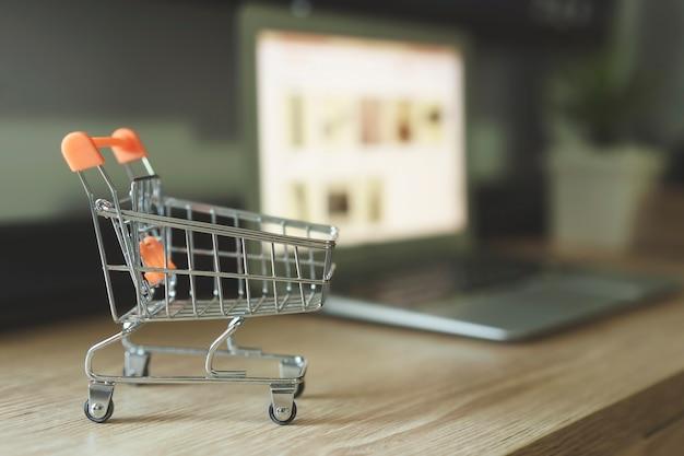 Concept d'achat en ligne, panier avec ordinateur portable flou sur le bureau