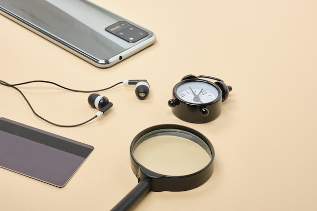 Concept d'achat en ligne. smartphone avec casque de carte de crédit, loupe, réveil sur fond beige