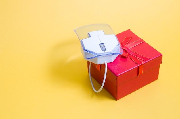 Concept d'achat en ligne, souris d'ordinateur et boîte-cadeau, fond jaune, espace copie