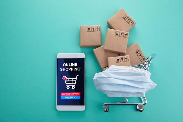 Concept d'achat en ligne. téléphone intelligent avec panier sur fond de menthe. quarantaine à domicile. vue de dessus.