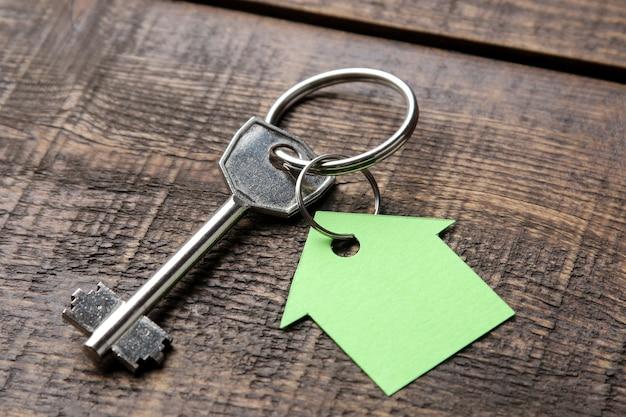 Concept d'achat d'une maison. clés avec porte-clés maison sur un gros plan de fond en bois brun.