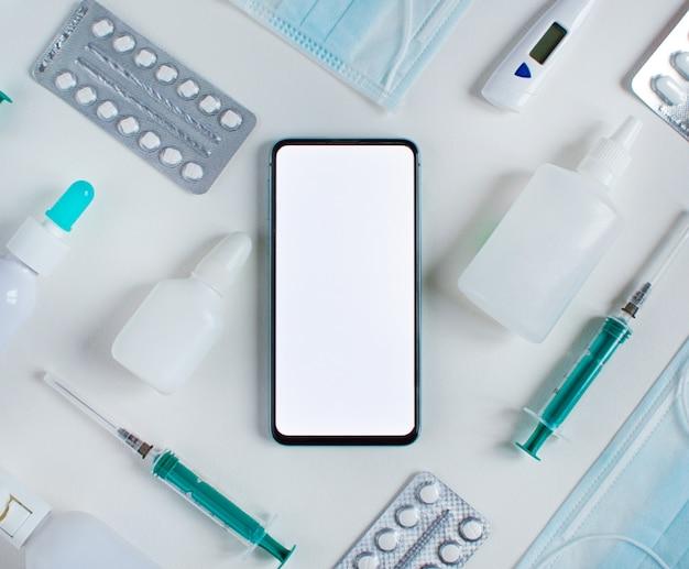 Concept d'achat de médicaments en ligne. téléphone et plat knollling gisaient sur blanc.