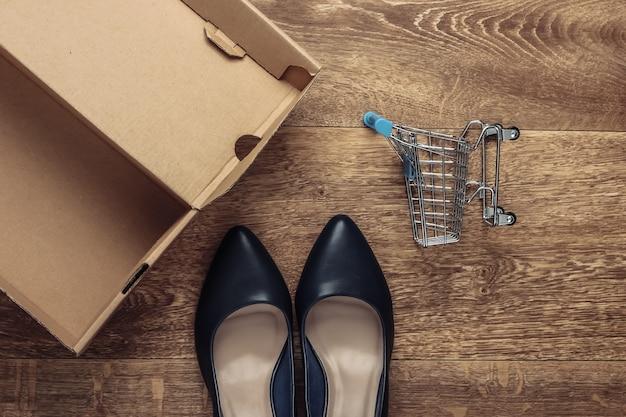 Concept d'achat. nouvelles chaussures à talons en cuir avec une boîte en carton, caddie sur le sol. vue de dessus
