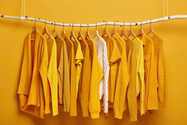 Concept d'achat de vêtements. ensemble de vêtements féminins sur étagère dans l'armoire.
