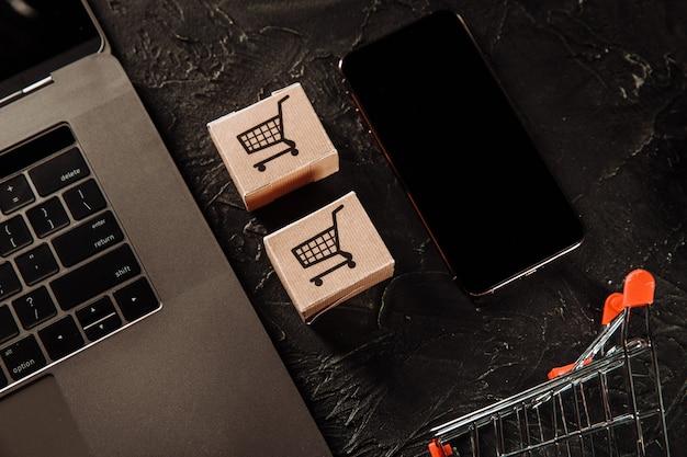 Concept d'achats en ligne. boîtes, ordinateur portable et smartphone sur une table grise.