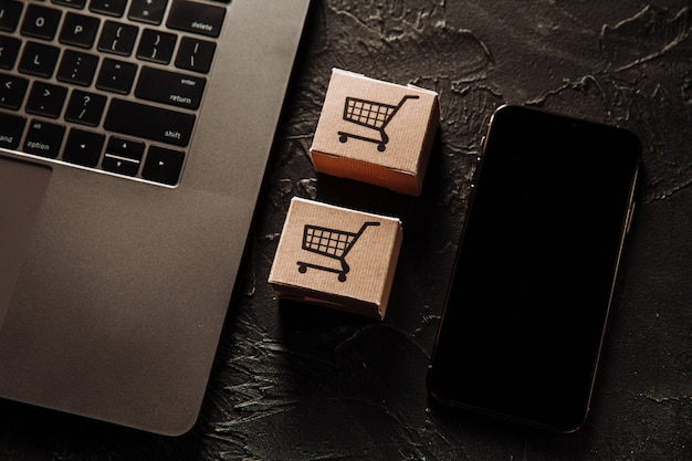 Concept d'achats en ligne. boîtes et smartphone sur un tableau gris.
