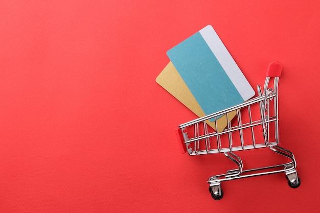 Le concept des achats en ligne. composition avec cartes de réduction et caddie sur fond rouge