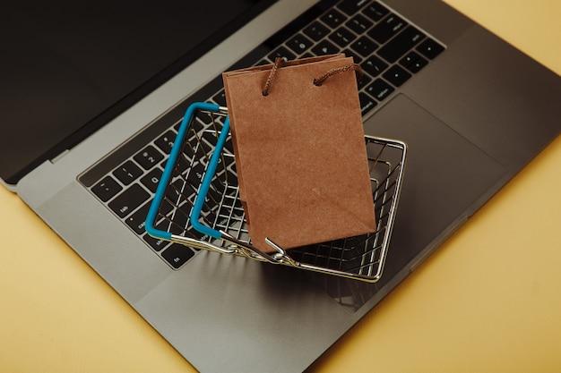 Concept d'achats en ligne. sac à provisions en papier et panier sur clavier d'ordinateur portable isolé sur jaune. vue de dessus.