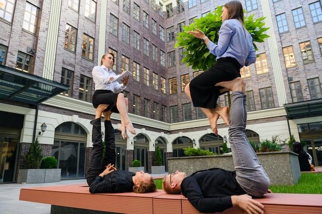 Concept d'acroyoga avec quatre personnes, deux hommes de la base allongés sur un banc à pied, deux filles volantes pendant le travail, parlant, prenant note, interviewant des vêtements de bureau