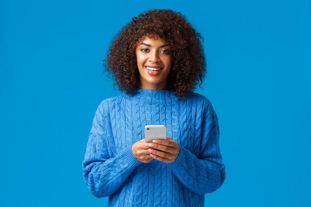 Concept d'addication de smartphone, de gen-z et de personnes. charismatique belle femme afro-américaine souriante avec coupe de cheveux afro en pull d'hiver