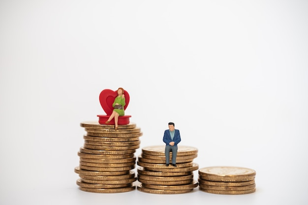 Concept d'affaires, d'argent, de famille et de planification. businesswoman figure miniature gens assis sur coeur rouge avec homme d'affaires sur le dessus de la pile de pièces d'or