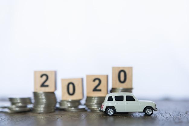 Concept d'affaires, d'argent et de finances du nouvel an 2020. grand plan, de, miniature, voiture blanche, jouet, à, bloc bois, nombre