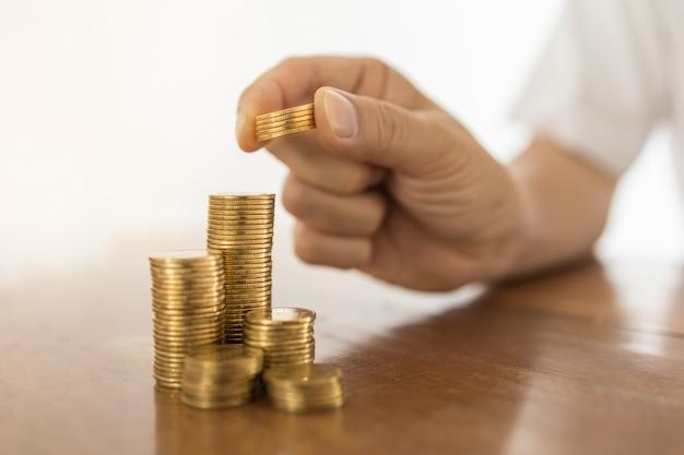 Concept d'affaires, d'argent, de finances, de sécurité et d'épargne. gros plan de la main de l'homme tenant et mettre cinq pièces en haut de la pile de pièces d'or sur la table en bois.