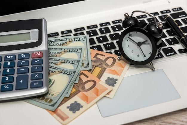 Concept d'affaires argent pour ordinateur portable dollars et euro avec horloge