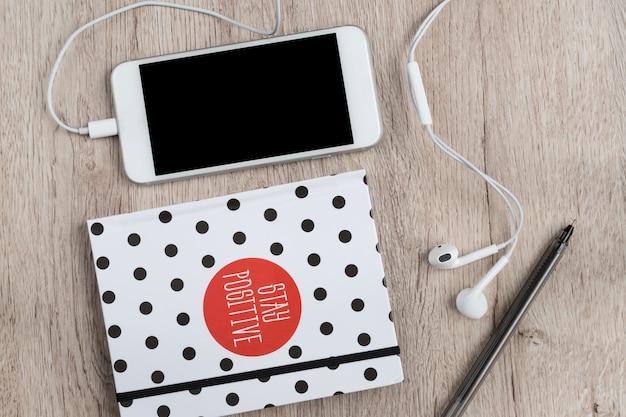 Concept d'affaires et de bureau - cahier vierge, smartphone et stylo noir sur la table en bois. lay plat minimal, vue de dessus.