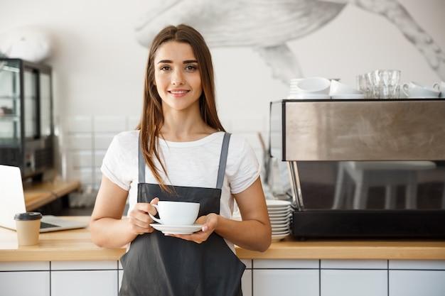 Concept d'affaires de café - femme de race blanche servant du café tout en restant dans un café. concentrez-vous sur les mains féminines en plaçant une tasse de café.